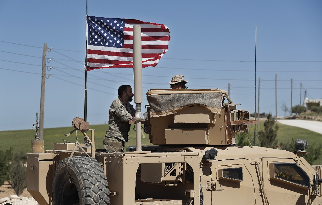 In this April 4, 2018 photo, a U.S-backed Syrian Manbij Military Council soldier, left, speaks with a U.S. soldier, at a U.S. position near the tense front line with Turkish-backed fighters, in Manbij town, north Syria. President Donald Trump's decision to withdraw troops from Syria has rattled Washington's Kurdish allies, who are its most reliable partner in Syria and among the most effective ground forces battling the Islamic State group. Kurds in northern Syria said commanders and fighters met into the night, discussing their response to the surprise announcement Wednesday, Dec. 20, 2018. (AP Photo/Hussein Malla)