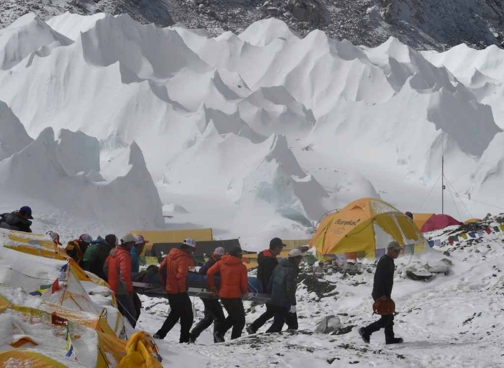 Rescue team personnel carry an injured person towards a waiting rescue helicopter at Everest Base Camp. ROBERTO SCHMIDT/AFP/Getty Images