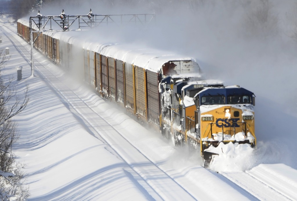 A CSX freight train plows its way past the Cemetery Rd. overpass in Lancaster, New York, Wednesday. AP Photo/Gary Wiepert