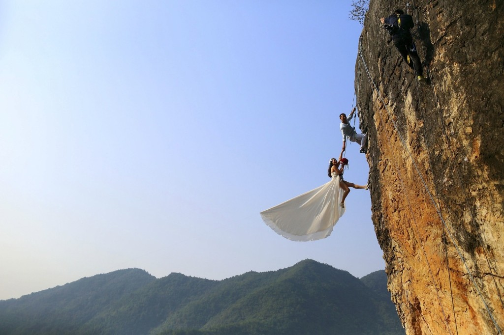 Zheng Feng, an amateur climber, takes wedding pictures with his bride on a cliff in Jinhua, Zhejiang province. REUTERS/China Daily