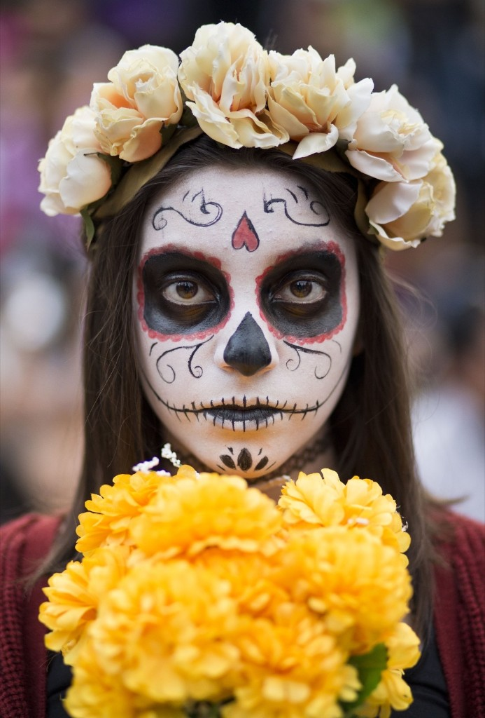 """A young girl with her face painted as a """"Catrina"""" takes part in a Day of the Dead celebration in Mexico City. AP Photo/Esteban Felix"""