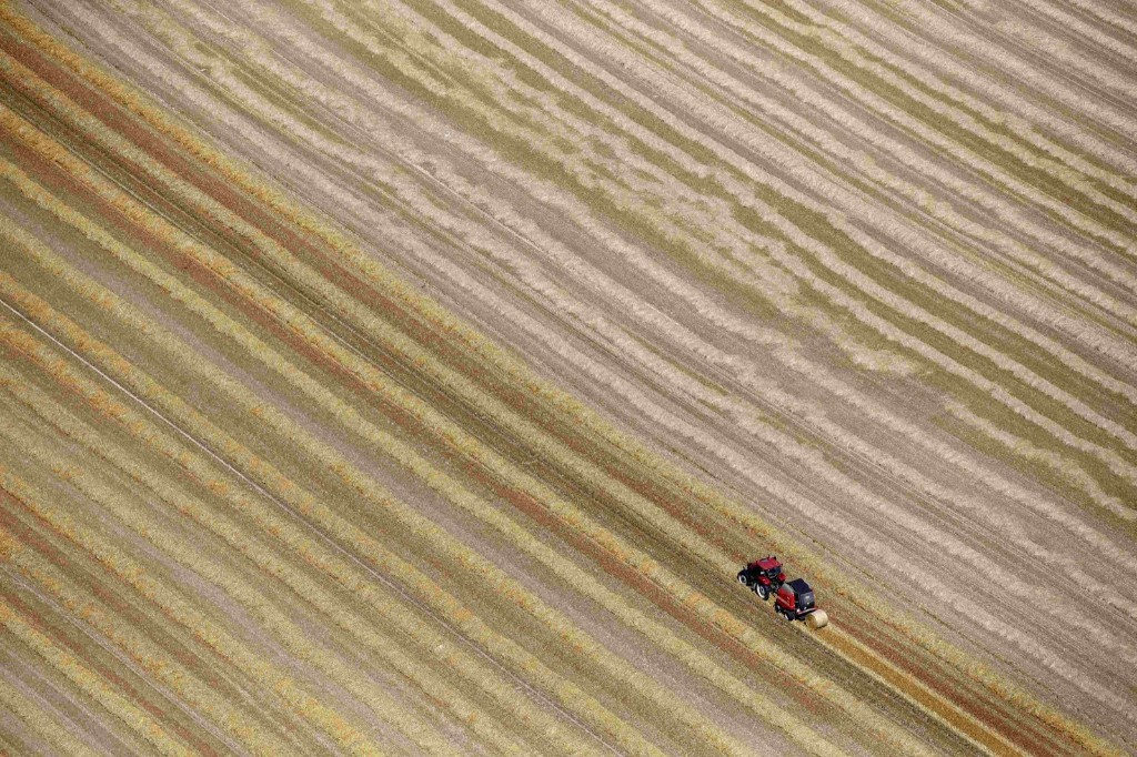 A French farmer in his tractor making bales of straw after wheat harvest in Coquelles, near Calais. REUTERS/Pascal Rossignol