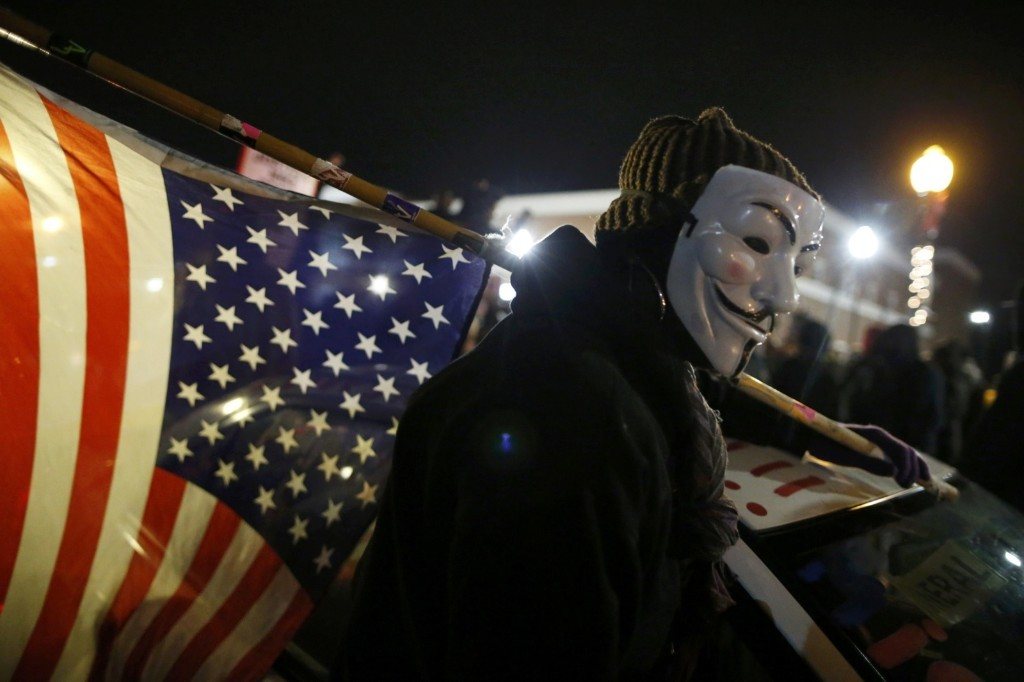 A protester wearing a Guy Fawkes mask carries an American flag outside the Ferguson Police Department. REUTERS/Jim Young
