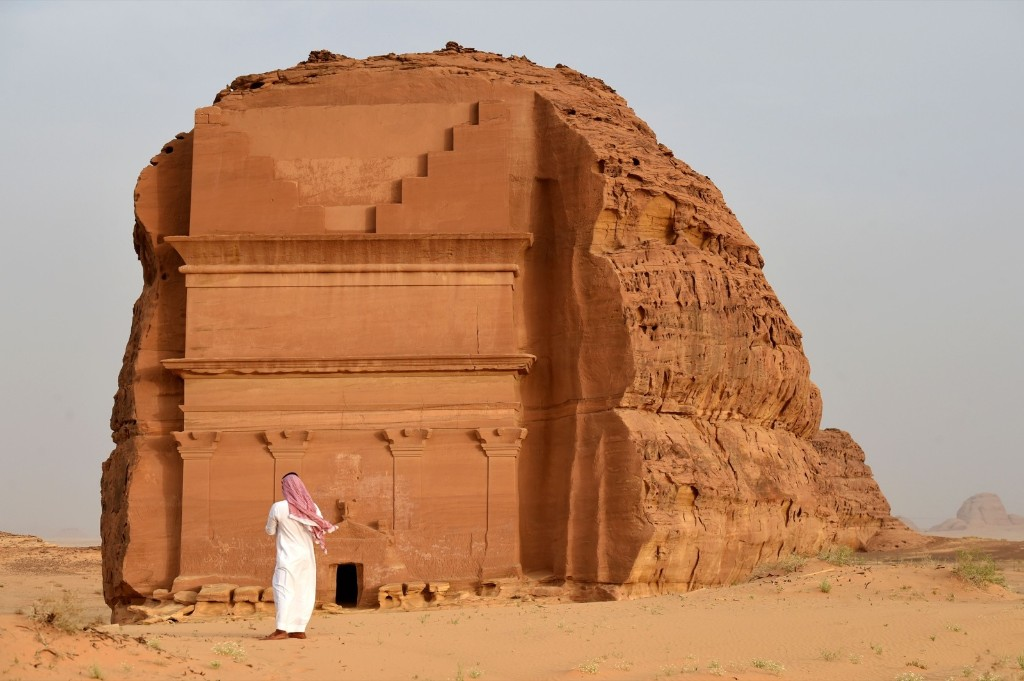 A man standing outside the Qasr al-Farid tomb (The Lonely Castle) carved into rose-coloured sandstone in Madain Saleh. FAYEZ NURELDINE/AFP/Getty Images