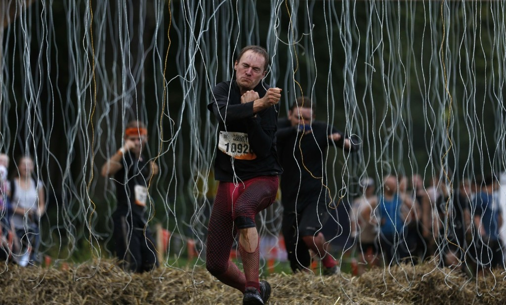 """A participant runs through the """"Electroshock Therapy"""" obstacle at the """"Tough Mudder"""" endurance event in Arnsberg, Germany. REUTERS/Ina Fassbender"""