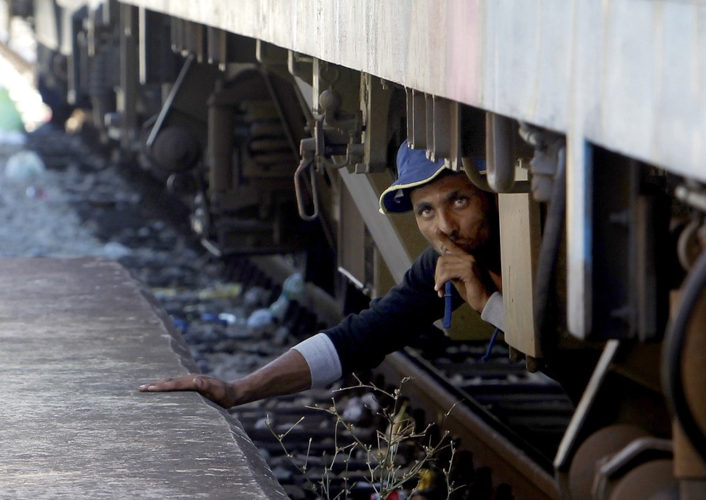 A migrant tries to sneak on a train towards Serbia at the railway station in the southern Macedonian town of Gevgelija. AP Photo/Boris Grdanoski