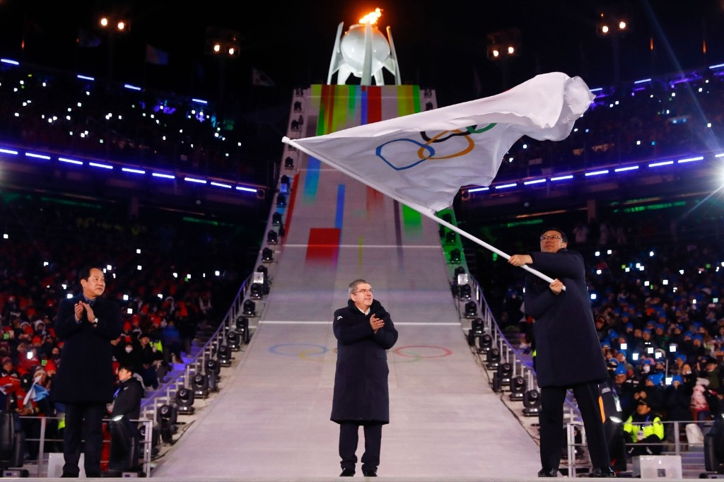 Mayor of Pyeongchang Sim Jae-guk (L) and the President of the International Olympic Committee Thomas Bach clap as the Mayor of Beijing Chen Jining waves the Olympic flag during the handover ceremony for the 2022 Beijing Winter Olympic Games. KAI PFAFFENBACH/AFP/Getty Images