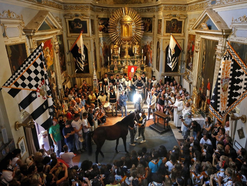 Supporters look at jockey Jonathan Bartoletti and his horse, Bened of the Lupa during a blessing ceremony in a church, before the Palio race in Siena August 17. Every year on July 2 and August 16, almost without fail since the mid-1600s, 10 riders compete bareback around Siena's shell-shaped central square in a bid to win the Palio, a silk banner depicting the Madonna and child. The race was postponed to August 17, 2015 due to rain. REUTERS/Fabio Muzzi