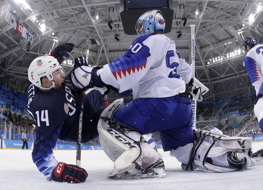 Goalie Jan Laco of Slovakia checks Broc Little of the U.S. during the third period of the qualification round of men's hockey. AP Photo/Julio Cortez/Pool