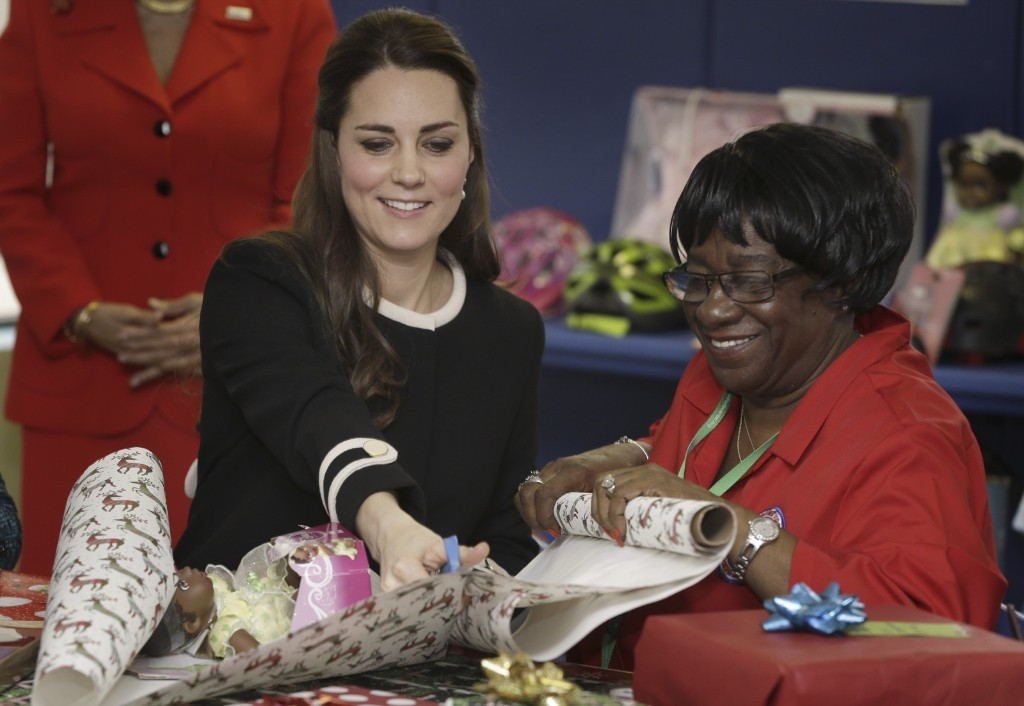 Kate, the Duchess of Cambridge wraps presents for children with volunteer Mary Dawkins at the Northside Center for Childhood Development in Monday in New York. AP Photo/Seth Wenig-Pool