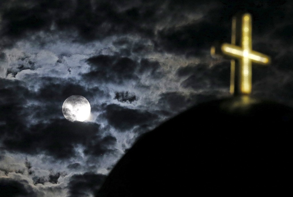 The moon rises above a church on Santorini. Greece's last-minute overtures were not enough to save the country from becoming the first developed economy to default on a loan with the International Monetary Fund. REUTERS/Cathal McNaughton