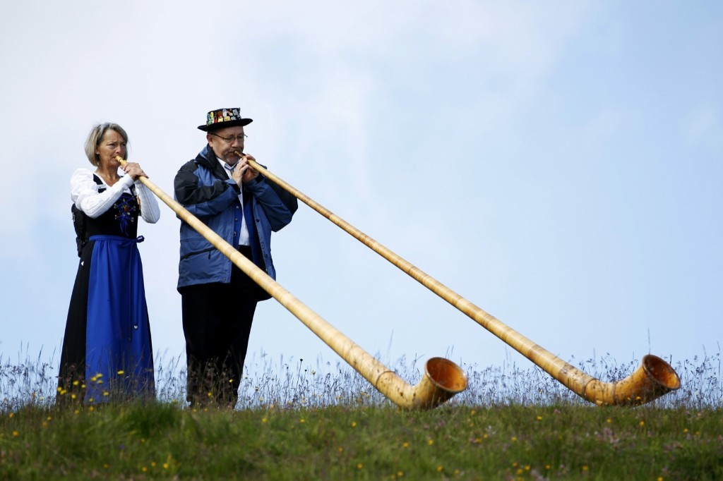 Alphorn blowers perform an ensemble piece at a festival on Lac de Tracouet near Nendaz, Switzerland. REUTERS/Pierre Albouy