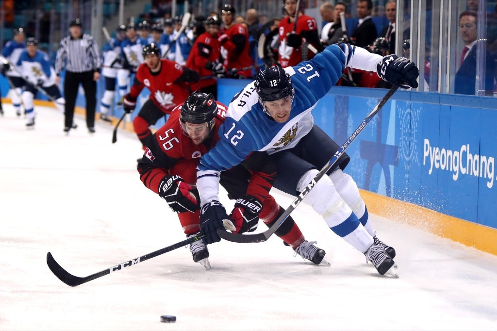 Maxim Noreau of Canada and Marko Anttila of Finland compete for the puck in the third period. Ronald Martinez/Getty Images