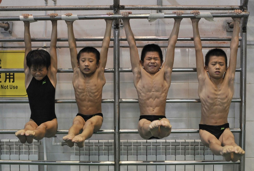 Young divers stretch as they hang from a steel bar during a training session at a sports school in Hefei, Anhui province. REUTERS/Stringer