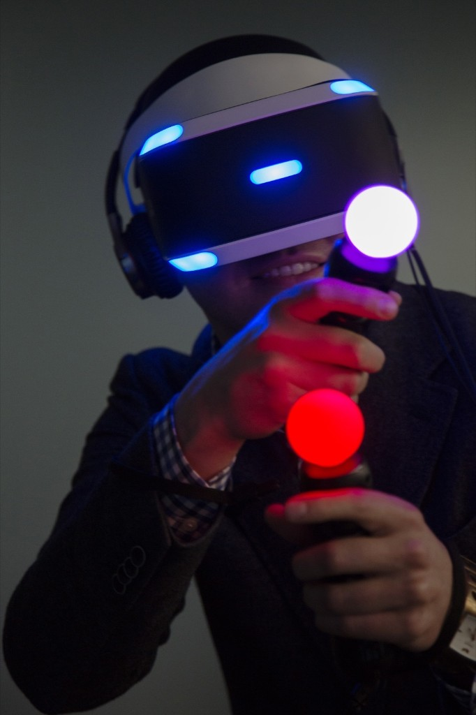 A member of the media plays a video game using a Sony Computer Entertainment Inc. Project Morpheus virtual-reality headset and controllers during a demonstration in Tokyo. Noriyuki Aida/Bloomberg/Getty Images