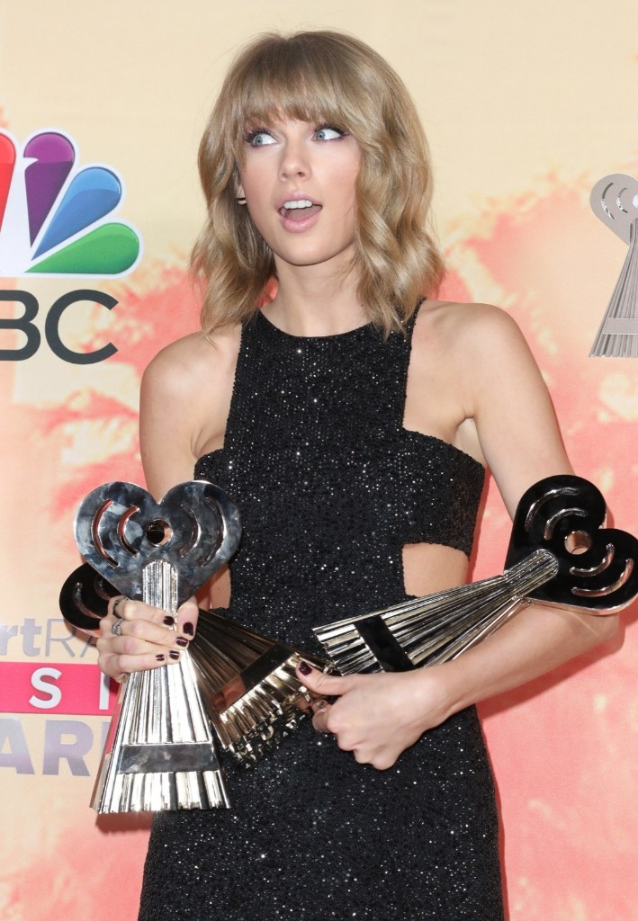 """Taylor Swift in the press room with the awards for best lyrics for """"Blank Space"""", song of the year for """"Shake It Off"""" and artist of the year at the iHeartRadio Music Awards, Sunday, in Los Angeles. John Salangsang/Invision/AP"""