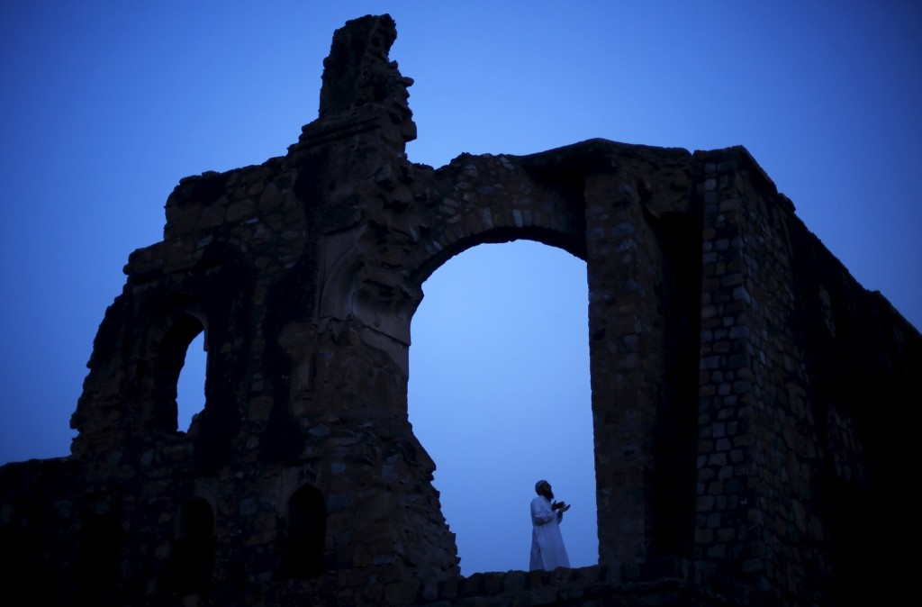 A Muslim man calls for the evening prayer after having his iftar (breaking of fast) meal during Ramadan at the ruins of the Feroz Shah Kotla mosque in New Delhi. REUTERS/Adnan Abidi