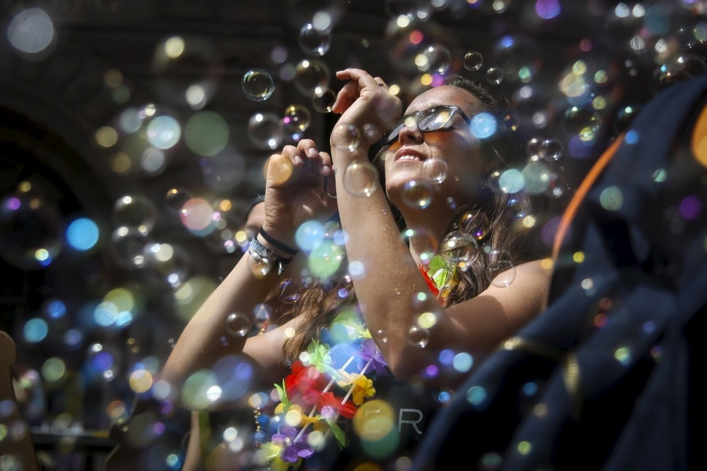 A woman dances in a cloud of bubbles while marching in the Gay Pride parade in San Francisco. REUTERS/Elijah Nouvelage