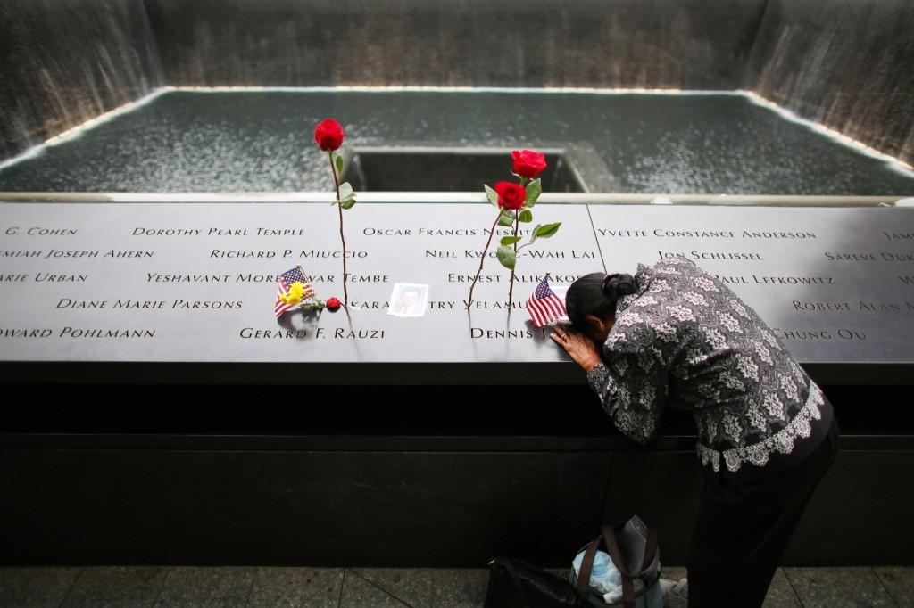 A woman grieves at her husband's memorial near the South Tower reflecting pool before Sept. 11 observances. Chang W. Lee/Pool