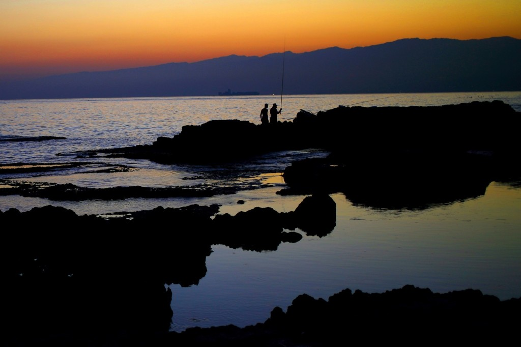 Lebanese anglers cast fishing poles from a rocky area along the Beirut coastline. AP Photo/Hassan Ammar