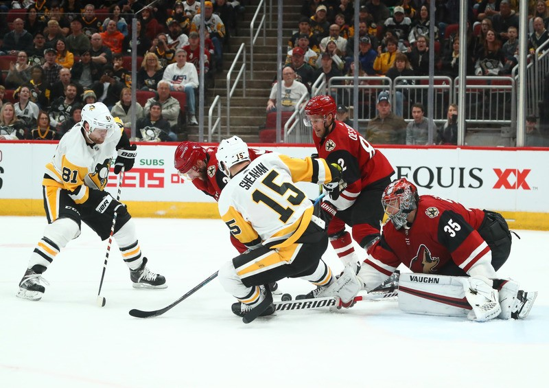Jan 18, 2019; Glendale, AZ, USA; Arizona Coyotes goalie Darcy Kuemper (35) defends the goal against Pittsburgh Penguins center Riley Sheahan (15) and right wing Phil Kessel (81) in the third period at Gila River Arena. Mandatory Credit: Mark J. Rebilas-USA TODAY Sports