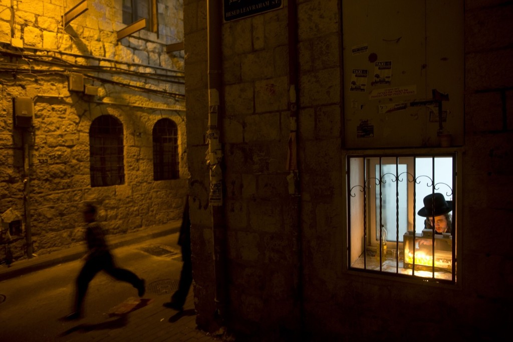 An ultra-Orthodox Jewish man lights candles during Hanukkah in Jerusalem's Mea Shearim neighborhood. AP Photo/Oded Balilty