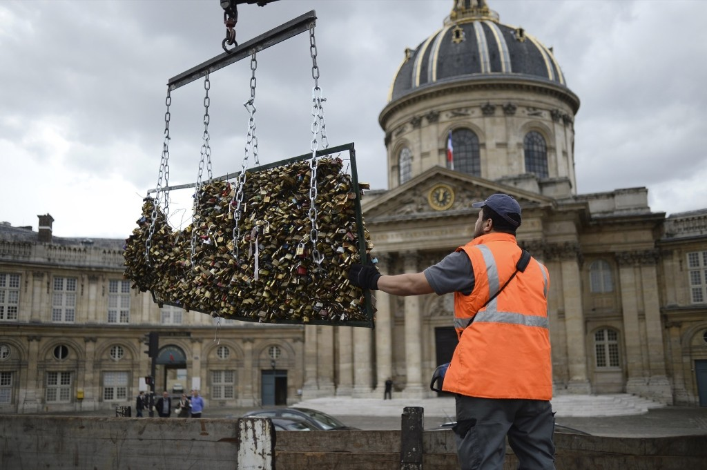 A worker removes 'love padlocks' attached on the railings of the Pont des Arts bridge, Monday, in Paris. Stephane de Sakutin/AFP/Getty Images