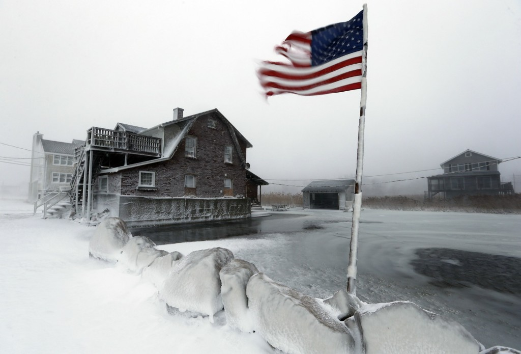 A tattered flag flies in a flooded yard along the shore in Scituate, Mass., Friday, after a brutal winter storm dropped nearly two feet of snow in the area. AP Photo/Michael Dwyer