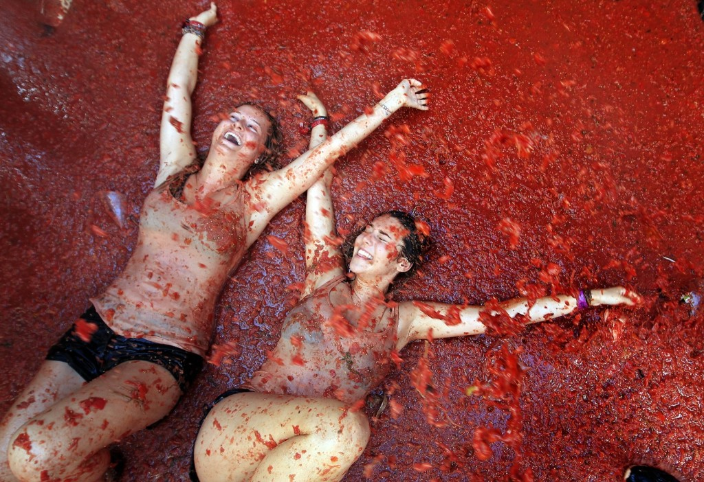 "Two woman lie in a puddle of squashed tomatoes during the annual ""tomatina"" tomato fight fiesta, in the village of Bunol, 50 kilometers outside Valencia, Spain, Wednesday. AP Photo/Alberto Saiz"