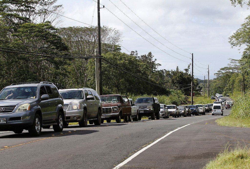 Residents of the Leilani Estates queue in a line to enter the subdivision to gather possessions from their homes, Sunday, May 6, 2018, in Pahoa, Hawaii. Scientists reported lava spewing more than 200 feet (61 meters) into the air in Hawaii's recent Kilauea volcanic eruption, and some of the more than 1,700 people who evacuated prepared for the possibility they may not return for quite some time. (AP Photo/Marco Garcia)
