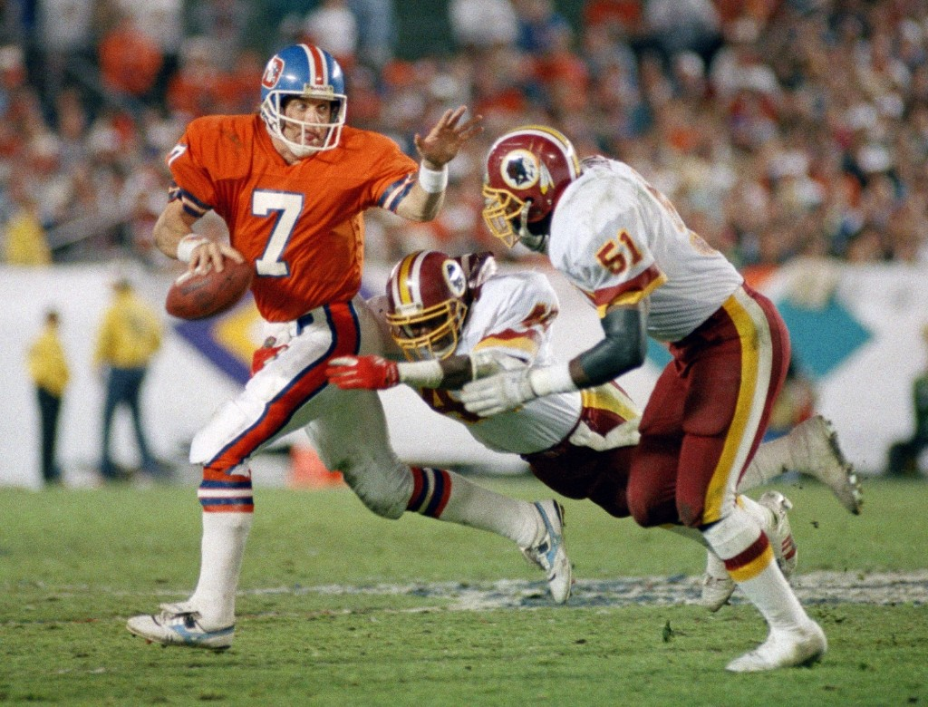 Broncos quarterback John Elway scrambles away from pressure by the Redskins Dexter Manley and Monte Coleman in Super Bowl XXII, Jan. 1988, in San Diego. Elway was sacked five times and threw three interceptions as the Broncos lost, 42-10. AP Photo