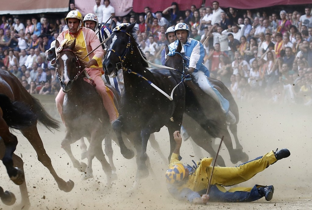 A rider falls during the ancient Palio of Siena, the famous break-neck bareback horse race run, in Siena, Italy, August 17. AP Photo/Paolo Lazzeroni