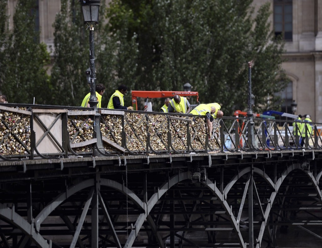 Workers remove love padlocks attached on the railings of the Pont des Arts bridge, Monday, in Paris. Stephane de Sakutin/AFP/Getty Images