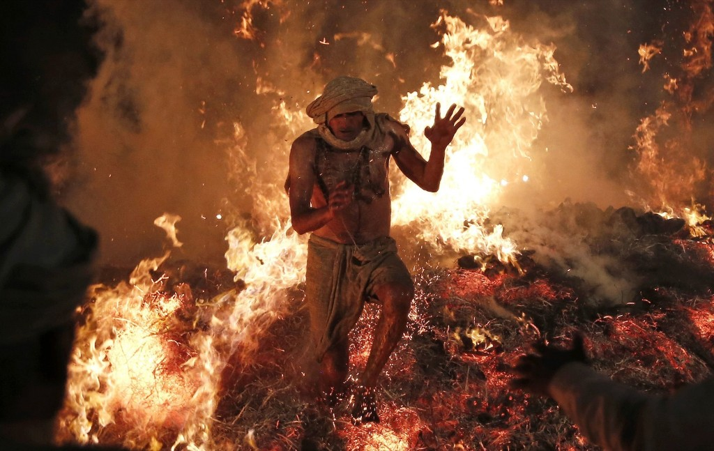 Hindu priest Babulal jumps out of a fire to signify the burning of the demon Holika in a ritual to mark the first day of Holi. REUTERS/Adnan Abidi