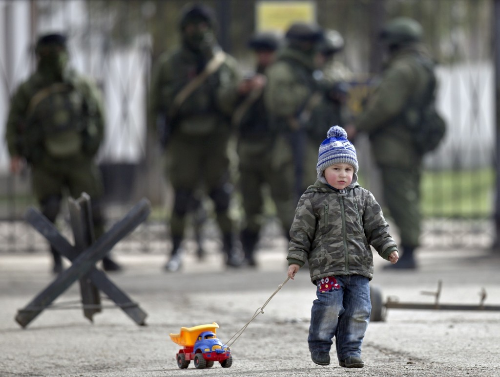 A child drags a toy truck past pro-Russian soldiers at a Ukrainian military base in Perevalne, Crimea. AP Photo/Vadim Ghirda