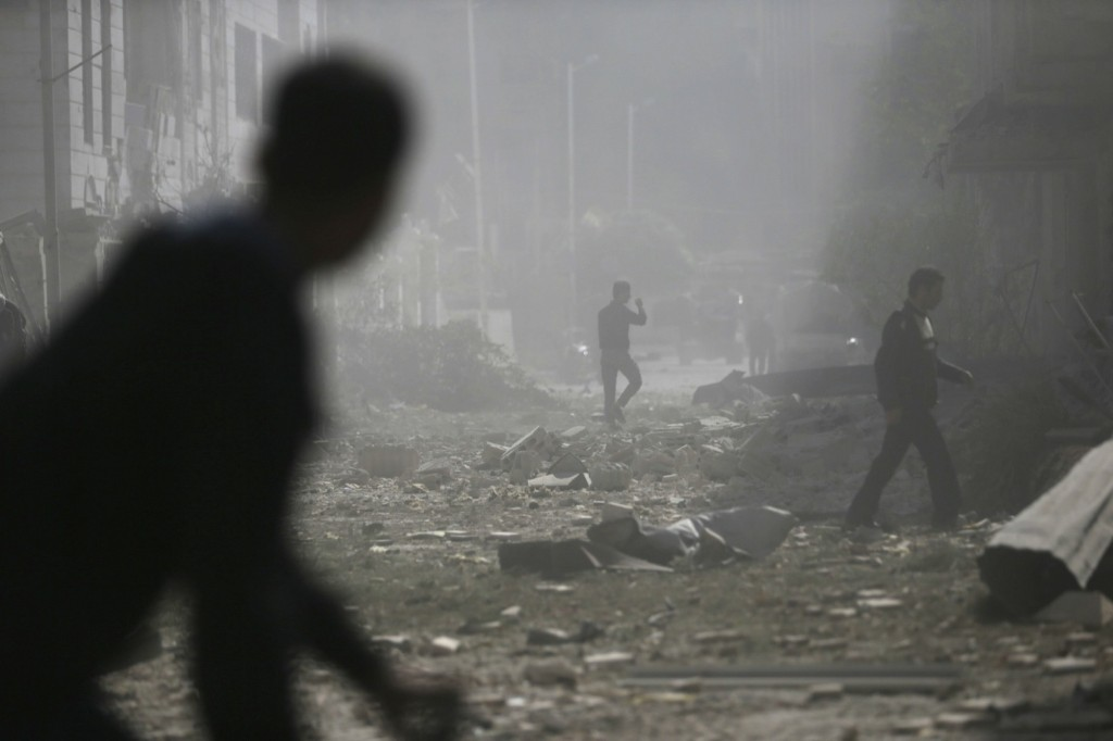Men walk on rubble at a site hit by what activists said were air strikes by forces of Syria's President Bashar al-Assad in Damascus. REUTERS/Bassam Khabieh