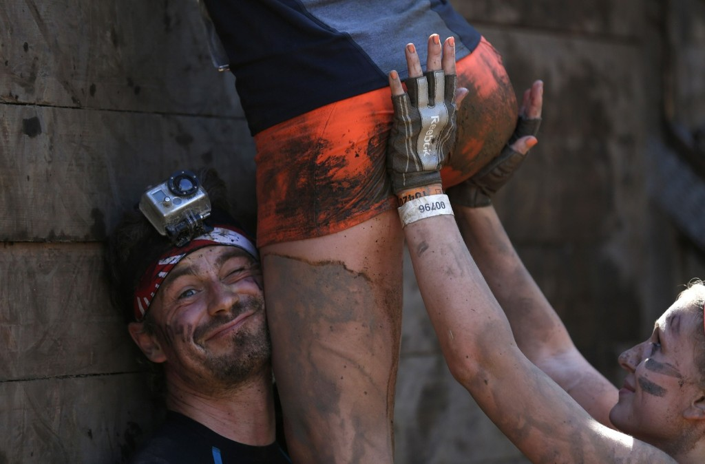 "Participants climb over a wall at the ""Tough Mudder"" endurance event series in Arnsberg, Germany. REUTERS/Ina Fassbender"