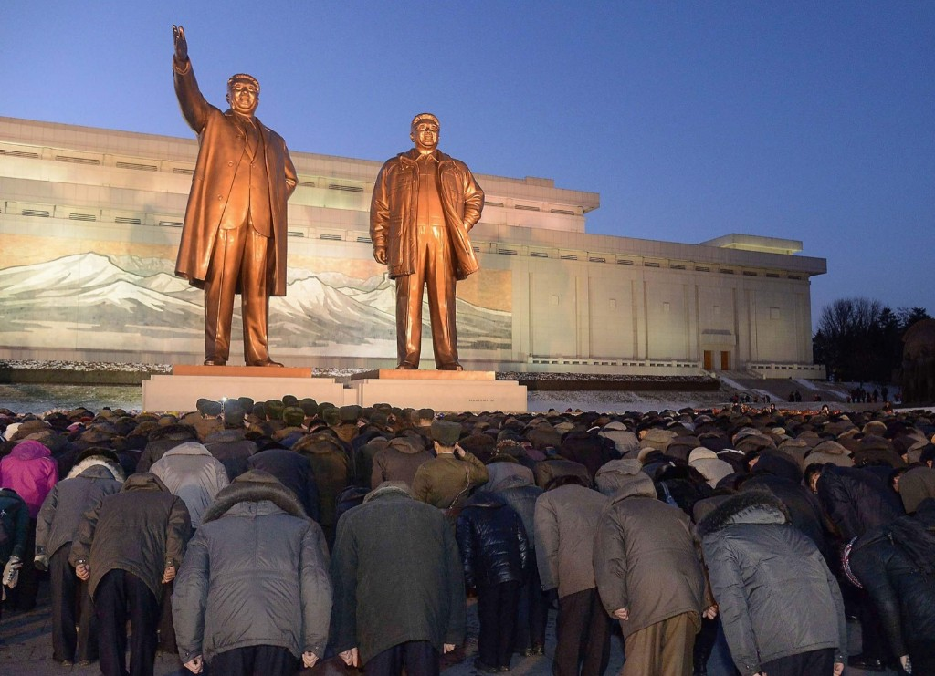North Koreans bow to bronze statues of founder Kim Il Sung and leader Kim Jong Il at Mansudae in Pyongyang. REUTERS/Kyodo