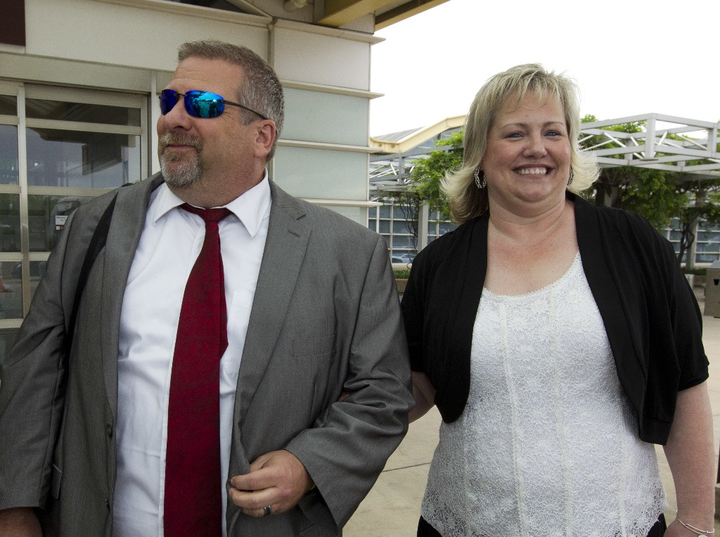 FILE - In this May 26, 2018, file photo, Laurie Holt, right, and Jason Holt arrive at Ronald Reagan Washington National Airport in Arlington, Va., to meet their son, Joshua Holt. Laurie Holt, a Utah woman who spent nearly two years pushing to get her son freed from a Venezuelan jail, has died at age 50. (AP Photo/Jose Luis Magana, File)