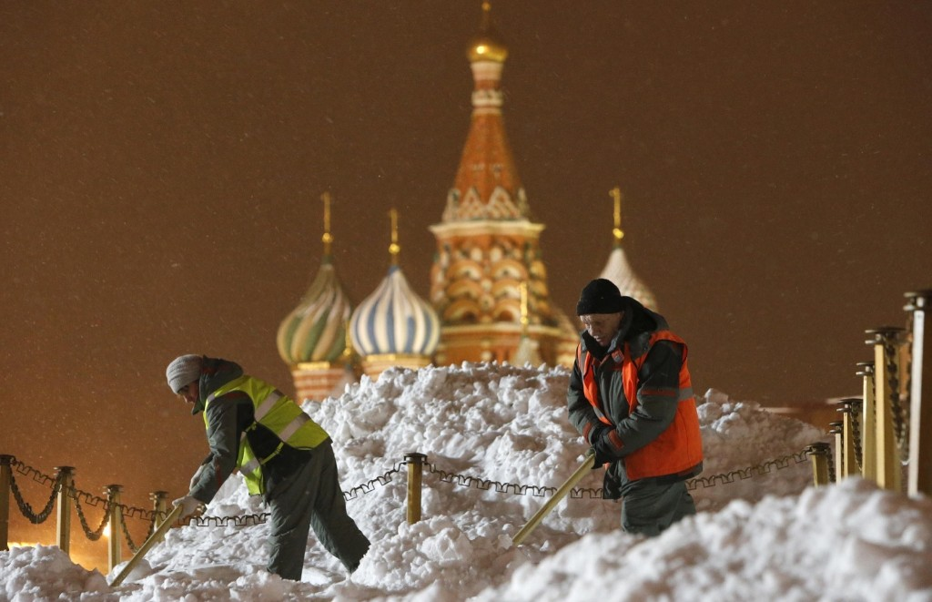 Workers clear snow in Red Square on Christmas Day. REUTERS/Sergei Karpukhin