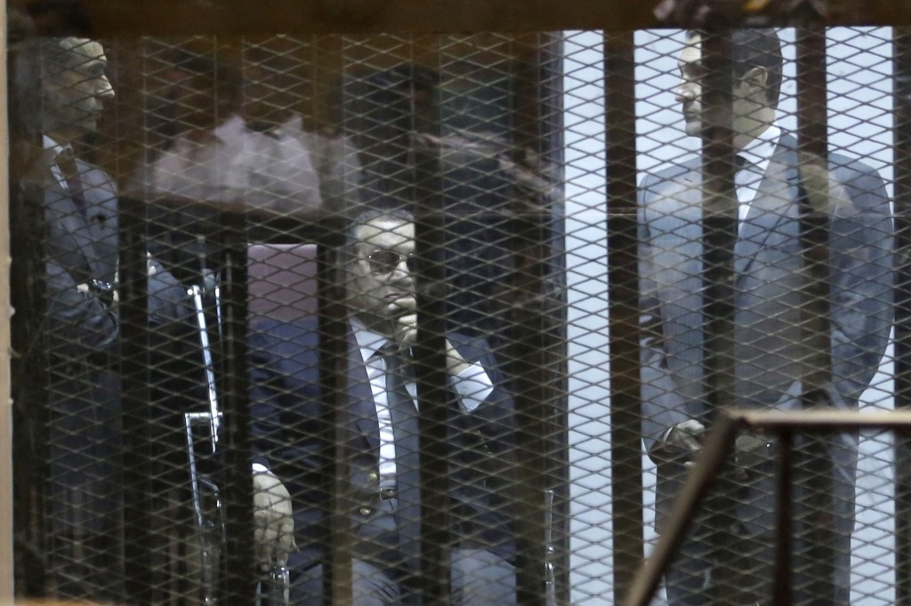 Former Egyptian President Hosni Mubarak and his two sons, Gamal and Alaa, attend the verdict of their corruption case. They were sentenced to three years in prison. AP Photo/Hassan Ammar