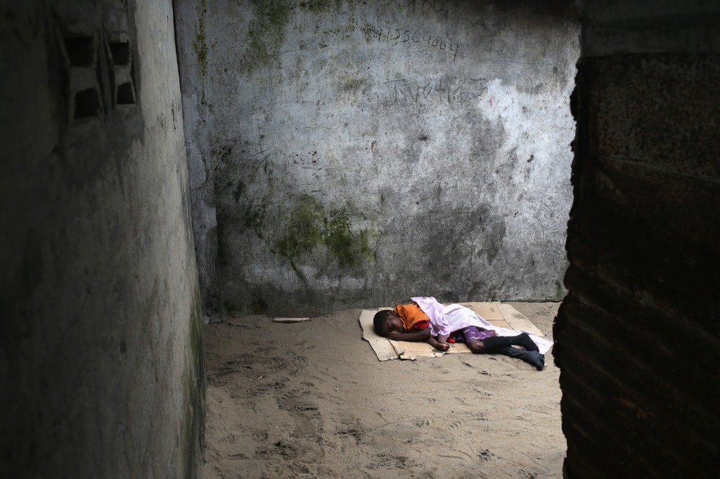 A very sick Saah Exco, 10, lies in a back alley of the West Point slum in Monrovia. John Moore/Getty Images