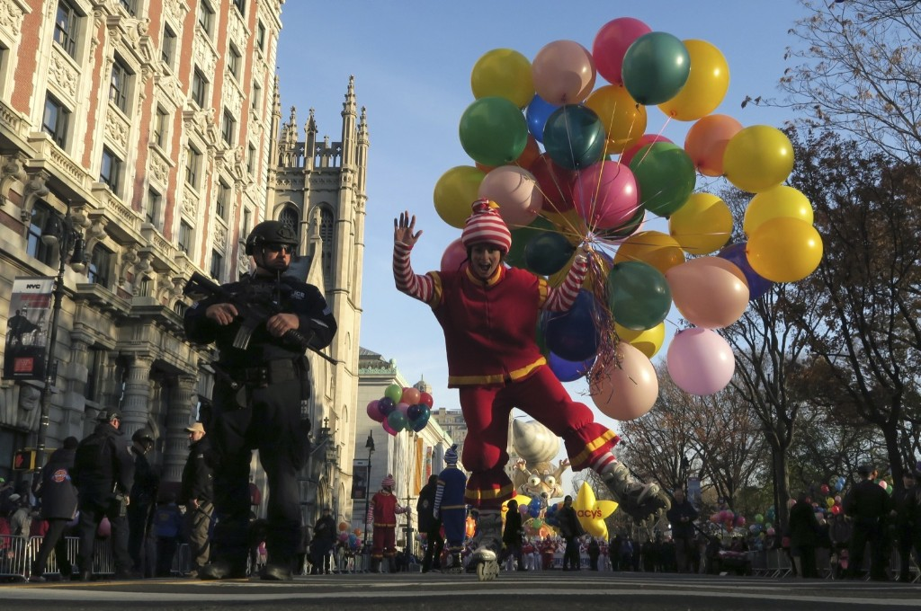 A clown with balloons skates past a New York City police officer at the start of the Macy's Thanksgiving Day Parade in New York, Thursday. Photo by Gary Hershorn