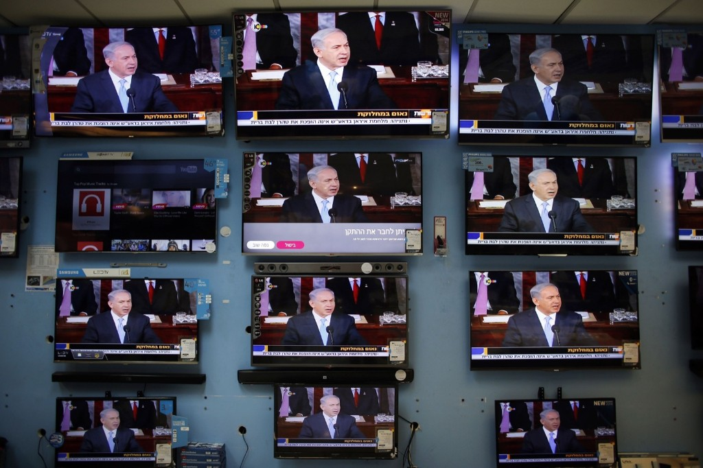 Israel's Prime Minister Benjamin Netanyahu is seen delivering his speech to the U.S. Congress on television screens in an electronics store in a Jerusalem, Tuesday. REUTERS/Ronen Zvulun