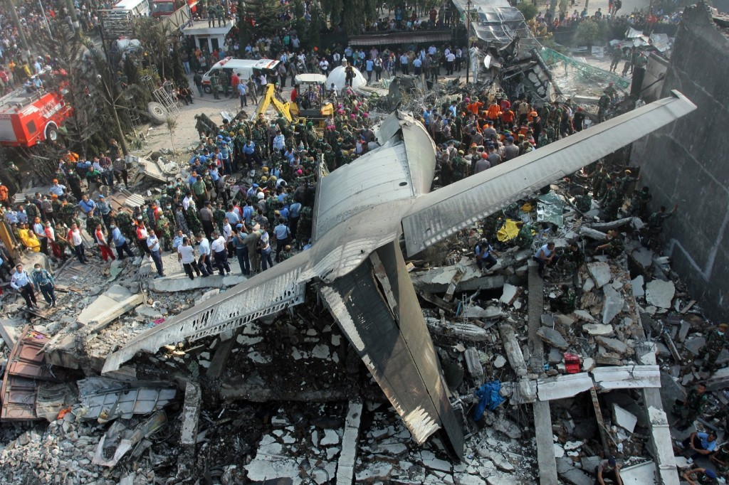 Rescuers search for victims where an air force cargo plane crashed in Medan, North Sumatra, Indonesia. AP Photo/Yudha Lesmana