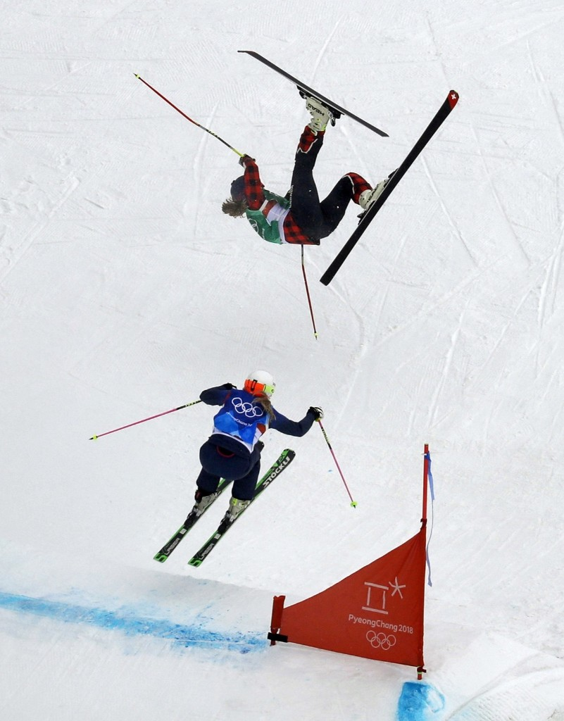 India Sherret of Canada crashes as Emily Sarsfield of Britain jumps during the women's ski cross elimination round. AP Photo/Kin Cheung