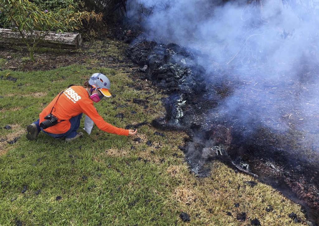 In this Sunday, May 6, 2018 photo provided by the U.S. Geological Survey, a Hawaii Volcano Observatory (HVO) geologist collects samples of spatter for laboratory analysis in the Leilani Estates subdivision near Pahoa on the island of Hawaii. Kilauea volcano has destroyed more than two dozen homes since it began spewing lava hundreds of feet into the air last week, and residents who evacuated don't know how long they might be displaced. The decimated homes were in the Leilani Estates subdivision, where molten rock, toxic gas and steam have been bursting through openings in the ground created by the volcano. (U.S. Geological Survey via AP)