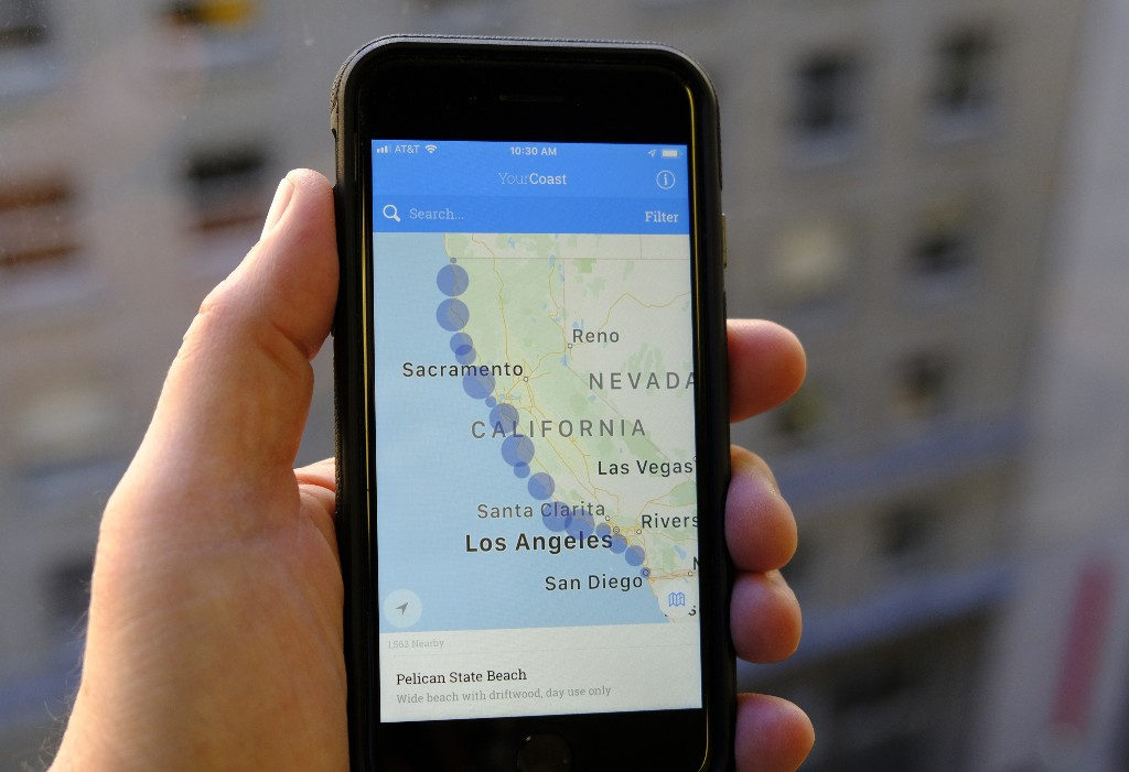 The new YourCoast app is displayed on a smartphone Thursday, Dec. 13, 2018, in San Francisco. The new smartphone app that shows users a map of more than 1,500 access points along the California coast was created with help from a tech billionaire whose elaborate wedding ran afoul of state regulators. The California Coastal Commission is unveiling the YourCoast app Thursday. (AP Photo/Eric Risberg)