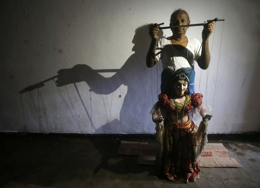 Maestro puppeteer Premin poses for a photograph with one of his creations before start of a show in Colombo. REUTERS/Dinuka Liyanawatte