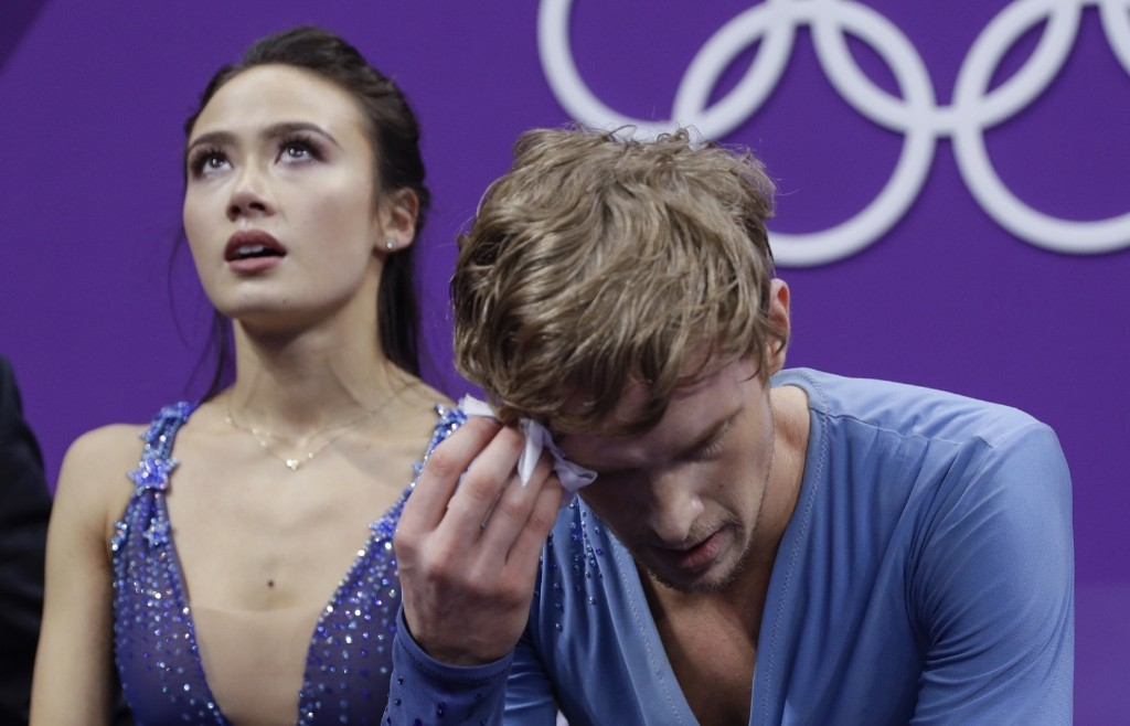 Madison Chock and Evan Bates of the U.S. wait in kiss and cry for their scores after a disappointing skate. They finished ninth. AP Photo/David J. Phillip